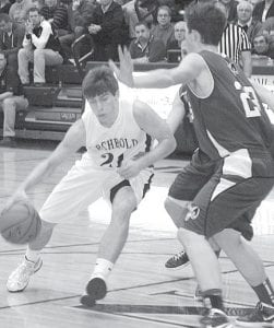 Tanner Wyse's drive to the basket is blocked by Tinora's Sam Lehman, right.– photo by Scott Schultz