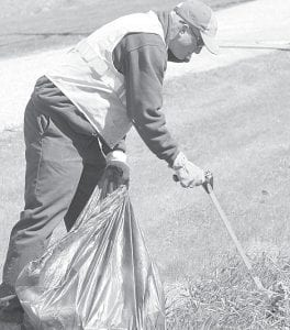 Jake Wyse, an Archbold Street Department employee, picked up trash along Miller Avenue, Monday, March 26.– photo by David Pugh