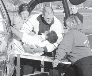 """While it has the look of a car accident, this scene was part of a simulation conducted by the Four County Career Center working with Northwest State Community College. It was held in an FCCC parking lot, Thursday, March 29. After volunteer victims adorned with stage-prop wounds were pulled from the wreckage, they were taken to the NSCC nursing lab, which was called """"Northwest Community Hospital"""" for the event. The victim, Aaron Brown, a student in the NSCC Law Enforcement & Security Tactics class, is pulled from the wreckage by Crystal Aeschliman, Bryan Tonneas, and Cindy Zachrich, from left. The three are paramedic students in the FCCC adult workforce public safety division.– photo by David Pugh"""