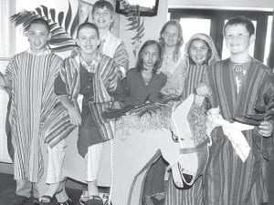 Youngsters at St. John's Christian Church, Archbold, prepare to reenact Christ traveling to Jerusalem on a donkey as part of Palm Sunday services, April 1. The Bible states the people laid palm fronds in Jesus' path, giving the day its name. Preparing for the processional into the sanctuary are, from left: Justin Lesniak, West Unity; Caleb Wooley, Archbold; TJ Rice, Archbold; Alexis Blankenship, Stryker; Tina Blankenship, Stryker; Kelsey Wyse, Archbold; and Aiden Warncke, Archbold. All are fifth or sixth graders.–photo by David Pugh