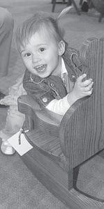 Libby Ringenberg, 3, Bryan, granddaughter of Steve Ringenberg, Fairlawn Haven executive director, tries out a new, handmade wooden chair at the Fairlawn Auxiliary Auction, Friday, March 30. The 2012 auction raised more than $39,000, which will be used to benefit patients at the retirement campus.– photo by David Pugh