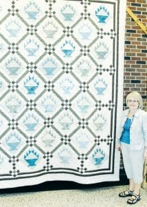 Glora Belle Yoder, an Archbold resident and PHS graduate, with the quilt she designed for this year's Pettisville Friendship Days, June 22-24. More than 50 women worked on the quilt, which will be raffled.– photo by David Pugh
