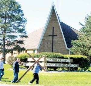 Several members of West Clinton Mennonite Church participated in a prayer walk Good Friday morning, April 6. Donna Friesen carries the cross, and is followed by Jeff Roth and Marcia Lehman.– photo by David Pugh
