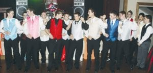 """Boys prepare to perform what can only be called """"The March of the Air Guitars,"""" as they get ready to walk across the dance floor while pretending to play rock guitars. From left: Tanner Rufenacht, Aaron Bruner, Aaron King, Josh Borton, Arrin Short, Travis Beck, Zach Pursel, Logan Beck, Kyle Beck, Tyler Herschberger, David Reyes, and Caleb Yoder. All are Pettisville students."""