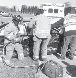 Archbold Rescue workers use the Jaws of Life to free Roger W. Brown, 65, Montpelier, from wreckage, Friday, April 6, when it was involved in a crash at the west intersection of US20A and Co. Rd. 24.– photo by David Pugh