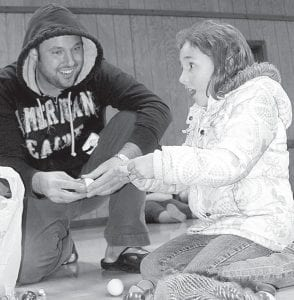 Amya Coulon, 7, Archbold, is shocked to discover she won a prize during the annual Flashlight Easter Egg Hunt, sponsored by Archbold Parks & Recreation, Saturday, March 31, in Ruihley Park. Looking on is her father, Chris. –photo by David Pugh