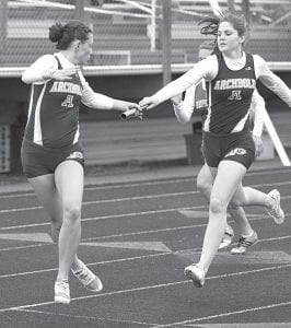 Jesse Fiddler passes the baton to Tressa Parsley in the girls 4x200 relay at the Napoleon Invitational, Saturday, April 14.– photo by Donald Young