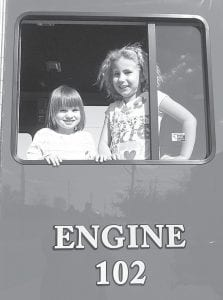 Trinity Lauber, 5, left, and Breanna Boysel, 7, Archbold, peer out from a window in the cab of the Archbold Fire Department fire truck, Friday, April 13. The girls' fathers are AFD firefighters.– photo by David Pugh
