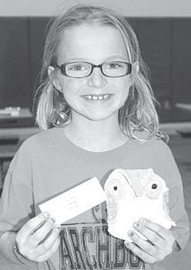 Young Artist Trinity Lichenwald, 7 1/2, an Archbold first grade student, shows off the owl she created in art class. Elementary students displayed their artwork during an art show, Thursday, April 19.– photo by David Pugh