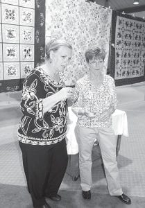The 36th annual Sauder Village Quilt Show is underway. The show opened Tuesday and closes Sunday. Founder's Hall was buzzing with activity on Monday as Village staff and volunteers set up the show. Left: Linda McCuean, left, and Linda Luggen, National Quilting Association certified judges, look over some of the 400 entries.