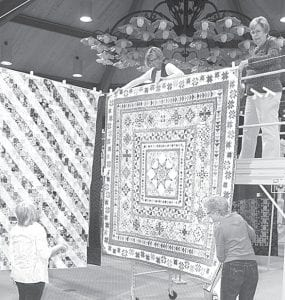 Volunteers hang quilts from wires stretched across Founder's Hall. Standing on the floor are Glora Belle Yoder, left, and Carolyn Snyder. On the scaffolding are Ginny Liechty and Cheryl Britsch.