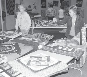 Kathy Day, left, and Luann Goertzen sort quilts yet to be hanged.– photos by David Pugh