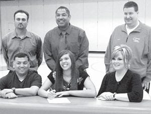 Hailey Galvan, AHS '10, signs a letter of intent to continue her basketball career at Marian University, Indianapolis, Ind. Sitting with Galvan are her parents, Roel and Dana. Back row, from left: Todd Bacon, MU head coach; Michael Llanas, Owens Community College head coach; and Stephen Perry, OCC assistant coach.– courtesy photo