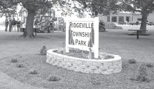 A nice sign and landscaping attract attention to the new Ridgeville Township Park in Ridgeville Corners. Local residents set up the first playground equipment, Saturday, April 21, adding to the picnic table and bench previously installed. Future additions are being planned.– photo by Pam Kruse
