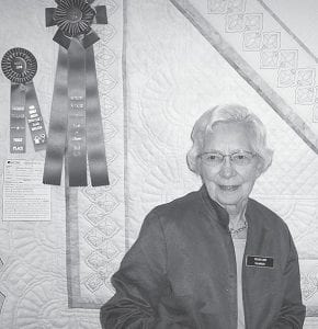 Velma Kamp, Archbold, with her quilt, featuring a design inspired by decorative tiles found in Uzbekistan. The quilt won Best of Show and a people's choice award during the annual Sauder Village Quilt Show, May 1-6. Approximately 400 quilts were shown during the event.– courtesy photo
