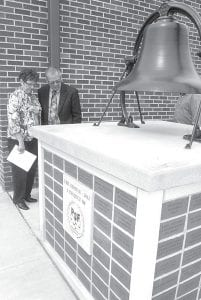 Marcine and Marlin Klopfenstein, rural Pettisville, look over the names of donors on plaques attached to a stand for the school district's original school bell. The donors are those who contributed to the new school atrium project; the bell is located just outside the atrium entrance. More than 300 people donated to the $935,000 project. The Klopfensteins visited the new Pettisville school during the building dedication and open house, Sunday, May 6.– photo by David Pugh