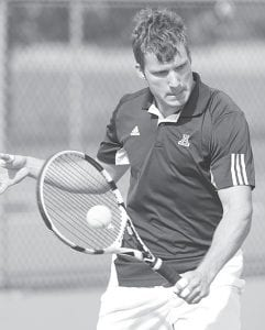 David Lauber concentrates and returns a backhand in AHS tennis action. Sectional tournaments begin this week.– photo by Mary Huber