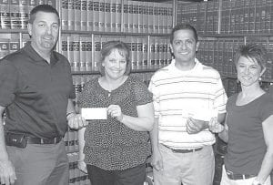 Archbold Park Board received donations from the Archbold Rotary Club and Archbold Area Foundation, Thursday, May 3, to fund its scholarship program, which reduces the cost of Archbold Parks & Recreation Department programs to low-income families. From left: Jeff Coressel, Rotary treasurer, presents a check to Jennifer Kidder, Parks & Recreation director, while Moses Rodriguez, of the Archbold Park Board, receives a check from Rachel Kinsman, a member of the Archbold Area Foundation Board.– photo by David Pugh