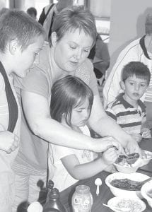 Ice cream with all the toppings was a big hit at the Archbold Band Ice Cream Social, Thursday, May 10. Top: Kelli Burkholder, Ridgeville Corners, helps daughter Ryann, 6, spoon some strawberries into a bowl, while at left, Kelli's son Gibson, 11, watches. Also looking on is Ian Grime, 6, Archbold. Right: Harrison Rohrs, 2, Ridgeville Corners, goes for a big bite.– photos by David Pugh