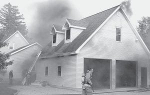 Smoke rises from a two-story garage at 101 Union Street as Archbold firefighters start their attack on the fire. The Monday evening, May 14 fire did about $35,000 in damage. There were no injuries. The cause is under investigation.– photo by David Pugh