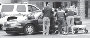 Archbold Rescue workers extricate the victim of a two-vehicle crash at the corner of Stryker Street and North Defiance Street in downtown Archbold, Saturday, May 12. The second vehicle involved in the mishap left the scene, but was later located by police.– photo by Mary Huber