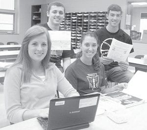 The Pettisville Agriculture Business II Class completed multiple projects for a Nutrients for Life Foundation contest and won $5000 from the Nourishing Our Planet in the 21st Century program. Representing the class, from left: Natalie Hubby, working on a Jeopardy-style Power Point training tool; Logan Beck, holding the check; Taylor Kruse, showing the curriculum materials provided by the Foundation; and Aaron Bruner, holding the flier the class created and shared. At the state FFA convention earlier this month, Pettisville was one of two Ohio FFA chapters winning the award.– courtesy photo