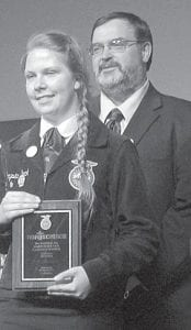 Chrysta Beck, with John Poulson, Pettisville FFA advisor, is recognized as a National FFA winner at the state FFA convention. Only seven students from Ohio were recognized. Beck won the animal science category, Division 1 (7-9th graders) at the agriscience fair.– courtesy photo