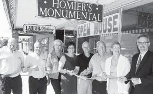 The ribbon was officially cut for the new location of Homier's Monumental, Inc., in the Lauber building in historic downtown Archbold, Friday, May 18. From left, Mike Kaminski and Andy Dominique, company representatives; Carrie Homier, advertising and marketing; Kathy and Mark Homier, co-owners; Tim Smith, owner, Lauber Clothing; Julie Brink, director of the Archbold Area Chamber of Commerce; and Jim Wyse, Archbold mayor.– photo by David Pugh