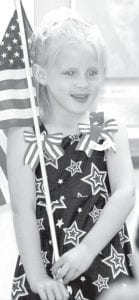 Jaci Ripke, 6, participates in the annual children's flag drill during the Ridgeville Corners Memorial Day program, Monday, May 28. She is the daughter of Bret and Tobi, rural Ridgeville Corners, and the granddaughter of Ted Ripke, commander, Ward L. Adams American Legion Post 454.– photo by Mary Huber