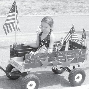 Sadie Swisher, 5, Pettisville, rides in a decorated wagon during the Pettisville Memorial Day Parade, Monday, May 28. Decorated wagons, bicycles, and tricycles are a parade tradition, which wends its way from the Pettisville PARC Pavilion to the Pettisville Cemetery.– photo by David Pugh