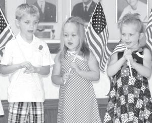 Mason Bickel, Izzy Henry, and Lexi Ripke, from left, perform during the children's flag drill at the Ward L. Adams American Legion Post 454 Memorial Day service, Monday, May 28, at Ridgeville Corners. The flag drill has been an annual part of the service for many years. All of the children are from Ridgeville Corners.– photo by Mary Huber