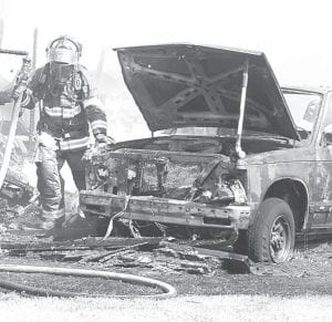 A firefighter walks past a burned-out pickup truck while mopping up after a Wednesday, May 30 fire north of Wauseon. Archbold firefighters provided mutual aid to Wauseon to fight a blaze at 15998 Co. Rd. J. Embers from a trash fire set a garage, mobile home, camper, and two vehicles ablaze. Marv Wheeler, WFD chief, said the call came in about 10:25 am. Morenci and Lyons fire departments also responded along. Wheeler estimated the damage at $5,000. He said Leo W. Etgen is the property owner; the tenant is Fred Sheldon.– photo by David Pugh