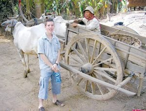 Andrew Pratt, PHS '06, spent a month in Cambodia teaching basic English skills as part of a research project for Defiance College. During graduation ceremonies in May, he received the Pilgrim Medal, DC's highest honor. Top: Pratt in Cambodia, with a wagon drawn by water buffalo. Right: Pratt helps a Cambodian woman with her English studies.– courtesy photos