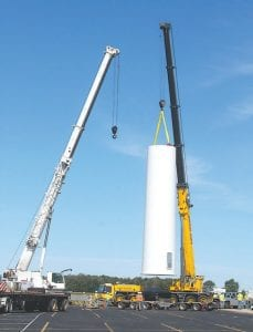 Heavy construction cranes lift the first section of the Archbold Area School District wind turbine tower into place, Wednesday, June 13. Additional tower sections are expected to be lifted into place later this week. When completed, the tower and nacelle will be over 200 feet tall.– photo by David Pugh
