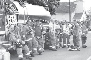 Archbold-German Township firefighters wait for their assignments at a house fire in Tedrow, Tuesday, July 3. The Wauseon Fire Department called Archbold for mutual aid. From left: Duane Beck, Gary Esterline, Russ Wyse, Charles Rowe, John Beldon, Matt Hines, Kris Lauber, Brian Engler, and Jamie Wyse.– photo by Mary Huber