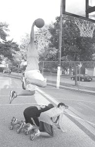 The 9-foot slam-dunk contest, a new event at the 2012 Carp Fest, allowed participants to show their basketball talents with a lower hoop. Jeff Sparks jumps over Caleb Wooley and D.J. Schroeder on his way to a dunk.– photo by Mario Gomez