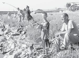 Luke Rosebrook, 8, is all smiles because he caught a fish at the Steve Schnitkey Fishing Derby, Saturday, July 21. His father, Mike watches. They are Archbold residents.– photo by David Pugh