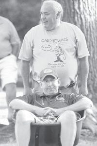 Allan Kinsman pushes fellow Lions Club member Randy Rufenacht in a wheelbarrow that was up for bids during the Friday night auction.– photo by Mary Huber