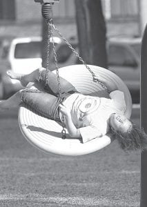Natalie Roth, 11, Archbold, takes a spin on a tire swing in Ruihley Park Friday evening.– photo by Mary Huber