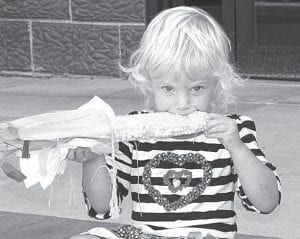 Winnie Browning, 2, Fayette, takes a break from children's activities and nibbles on corn on the cob Saturday afternoon.– photo by Mary Huber