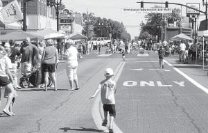 A youngster rushes toward the 2012 Carp Festival Kidz Zone, where pedal tractor pulling, art projects, and other activities await. It was the first year the 200 and 300 blocks of North Defiance Street were closed off to host most of the Saturday, July 21 Carp Fest events downtown. Julie Brink, Archbold Area Chamber of Commerce Director, said organizers were pleased.– photo by David Pugh