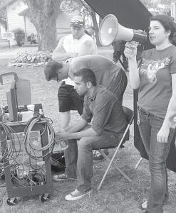 """Conrad Faraj, seated, director of the film, """"The Wind Is Watching,"""" on the set at Sauder Village, Monday, July 9. The independent film crew's goal is to be part of the Sundance Film Festival in Utah next year.– photo by David Pugh"""