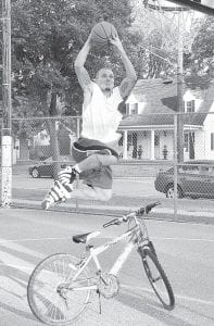 Tim Pickett, West Unity, jumps over a bike in the Slam Dunk contest at the Carp Festival.– photo by Mario Gomez