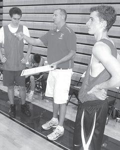Sean Lauber, center, coach of the Iroquois (N.Y.) High School Chiefs, talks strategy with his players during a break in their game against Pettisville, Friday, July 20. At left is Alex Popovski; at right, Matt Zimmerman. IHS is located outside Buffalo. Lauber brought the team to his hometown of Archbold so they could see where he grew up, and play some local teams.– photo by David Pugh
