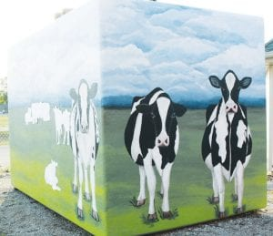 Above: the partially completed south and east sides of the freezer painted with a rural Henry County dairy farm mural. Left: Sue Hurst, Ridgeville Corners, adds some personal touches to one of the dairy cows on the mural.– photos by Mary Huber