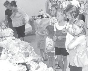 Above: Sisters and cousins admire some of the hundreds of dolls at the Sauder Village Doll Show & Sale, Sunday, Aug. 5. From left: Sami Speiser, 4, Chesterland; Elsie Mello, 4, Archbold; Sara Speiser, 9 Chesterland; Kaity Schnitkey, 8, Ridgeville Corners; Savanna Speiser, 9, Chesterland; and Meggie Mello, 7, Archbold. Below: Alexis Halker, 2, Antwerp, carried her own doll.– photos by David Pugh