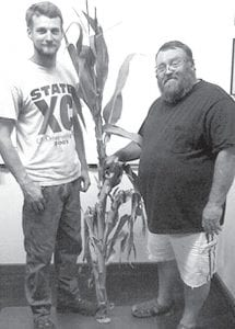 Whitney Stamm, left, and his father, Dale, with the six-eared corn stalk they found in one of their fields near West Unity. Whitney said generally, a corn plant will develop one or two ears, making this plant with six ears unique. Dale described the plant as a one-in-a-million mutation.– photo by David Pugh