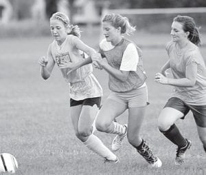 Above: Jensyn Garrow, Olivia Deskins, and Ashley Short, from left, go after a loose ball during the AHS girls soccer team practice, Thursday, Aug. 9.– photo by Mary Huber