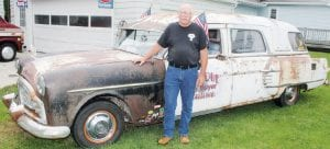"Dave Saam with his 1951 hearse. Rescued from a wrecking yard, Saam reassembled the vehicle from two other parts cars. The car is done in the ""barn fresh"" style, to appear as though it was just pulled out of a barn. ""I didn't want people to think The Addams Family had moved in next door,"" Saam said.– photo by David Pugh"