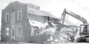 A hydraulic excavator attacks the former Gotshall Lumber Company building on Depot Street, Monday, Aug. 20. Gotshall Lumber was one of the first major businesses in the village. After the lumber company closed, it served as a construction company office, and later, an automotive machine shop.– photo by Mary Huber